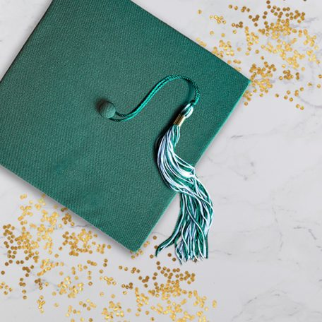 Green graduation cap with green and white tassel