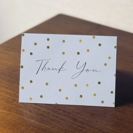 """Thank you card with script """"Thank you"""" and confetti dots sitting on a table"""