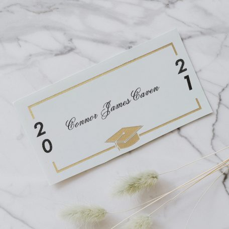 White name card with gold foil sitting on a marble table