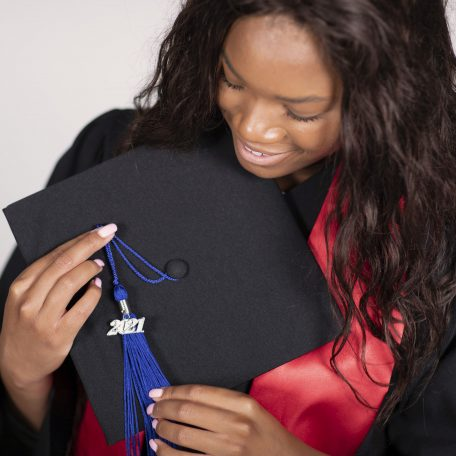 student wearing gown and stole holding her cap and tassel.